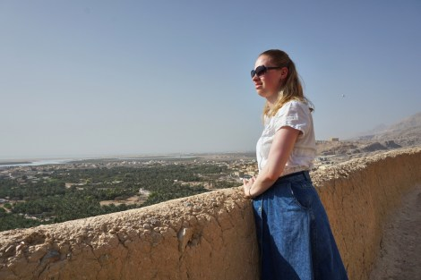 Girl standing next to wall overlooking landscape
