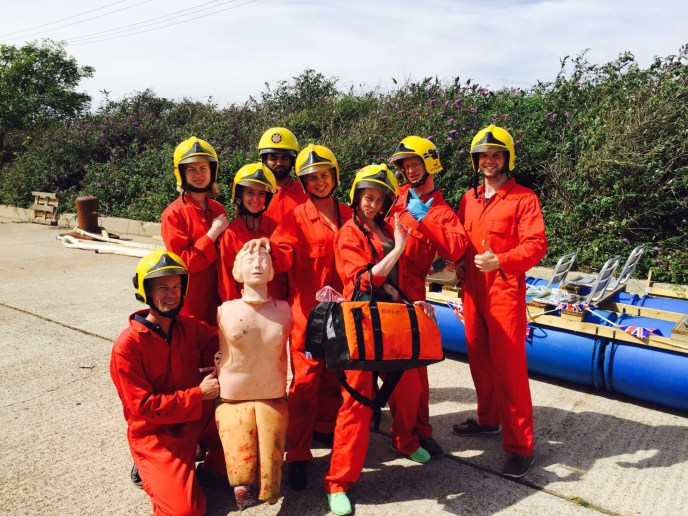 a group of people with a first aid dummy during an STCW course