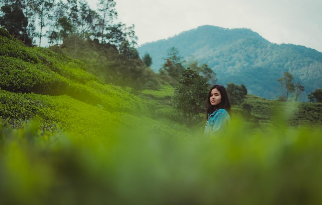 Woman of colour stands in a field with a mountain in the background