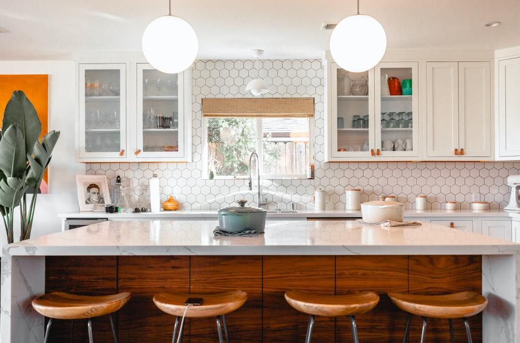 A bright, decluttered kitchen with wooden stools and a white backsplash