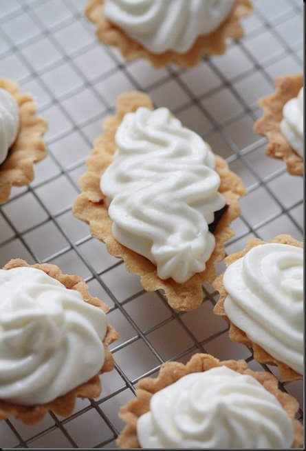 Tarts on a cooling rack topped with meringue.
