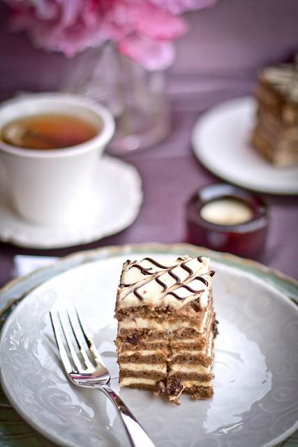 Piece of chocolate custard cake on a white decorative plate.
