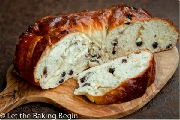 White Chocolate & Blueberry Bread wreath cut in half on a wooden board.