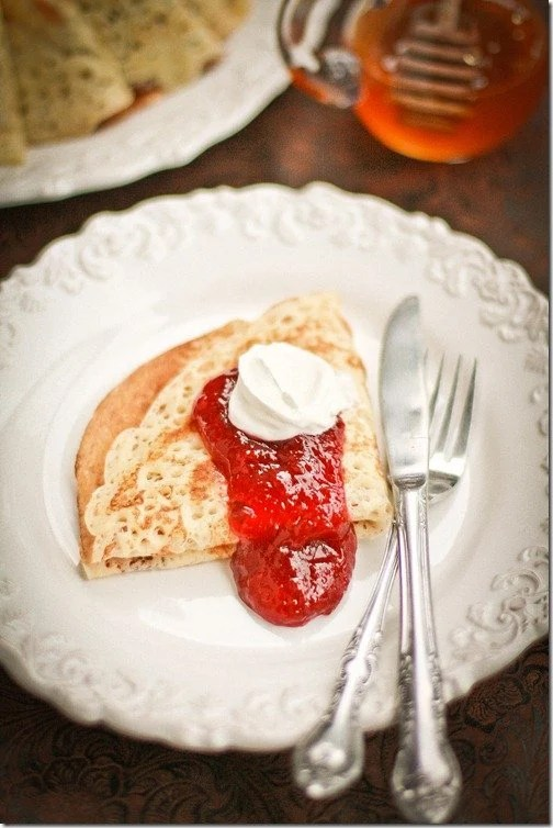 Blini topped with strawberry jam and sour cream on a white decorative plate with a fork and knife.