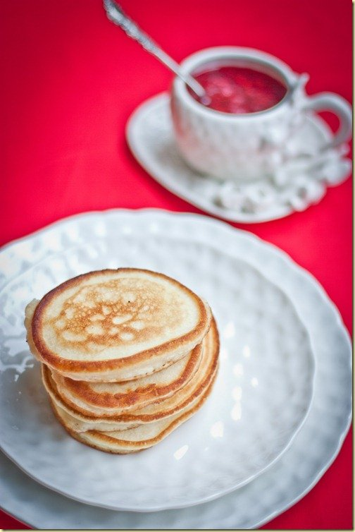 A stack of oladi or russian pancakes on a plate with Raspberry jam in the background.