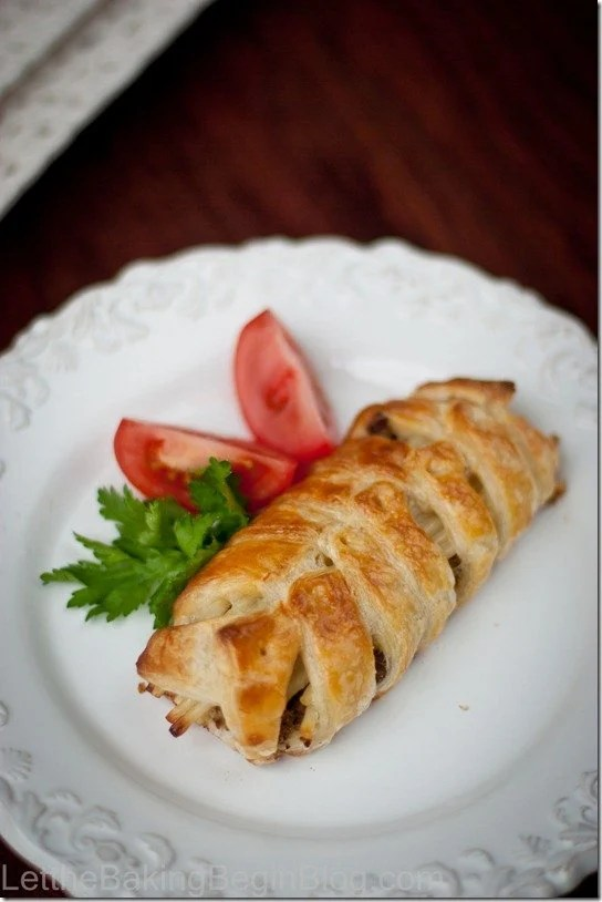 Braided meat pie recipe on a plate with tomato wedges