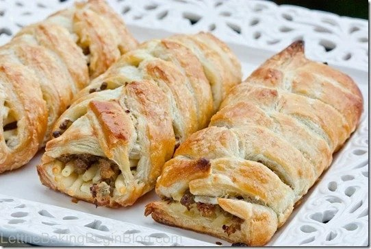 3 meat pastries filled with noodles and meat on a serving platter.