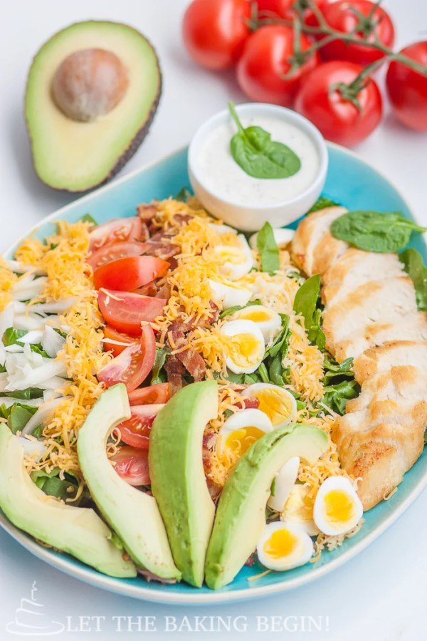 Cobb salad in a decorative bowl topped with all ingredients and fresh greens.