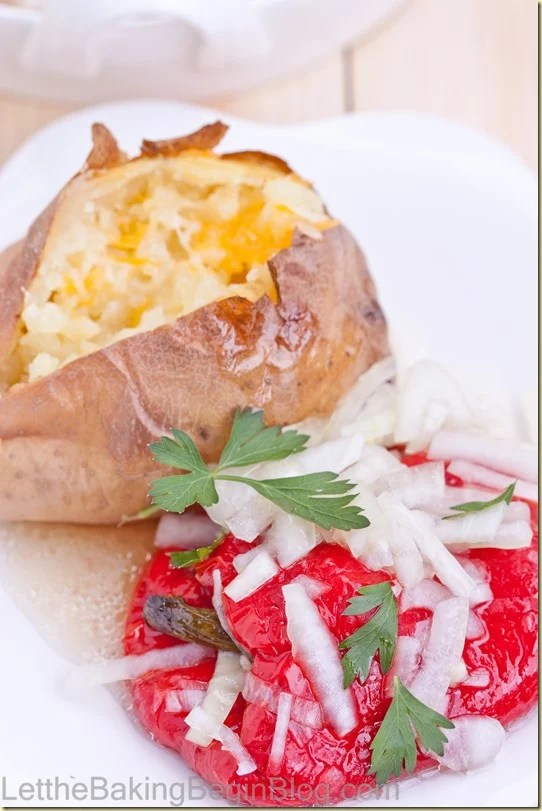 A red roasted pepper topped with sweet onion marinade sided with a baked potato on a white plate.