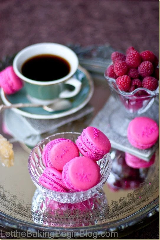 Raspberry scones in a glass bowl on a metal platter next to a cup of coffee.