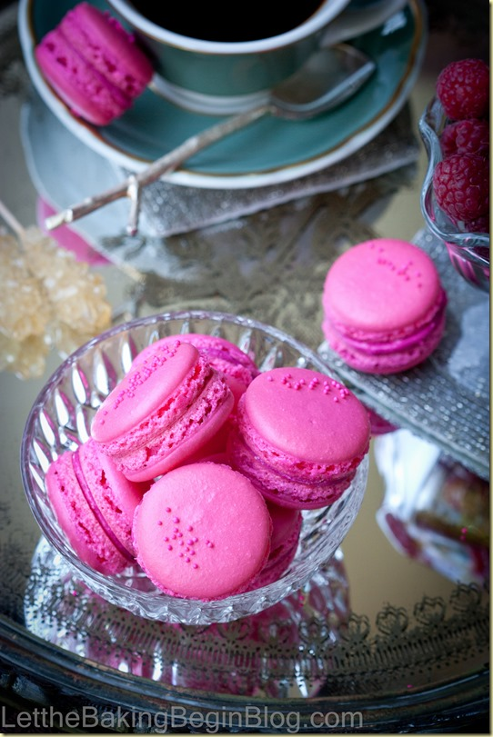 French macarons with raspberries in a glass bowl next to a cup of black coffee.