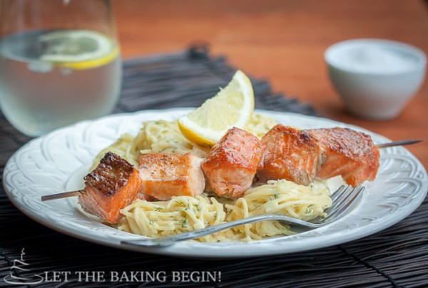 Side view of a bowl of spaghetti noodles and oven grilled salmon kabobs and a fresh lemon on a white decorative bowl.