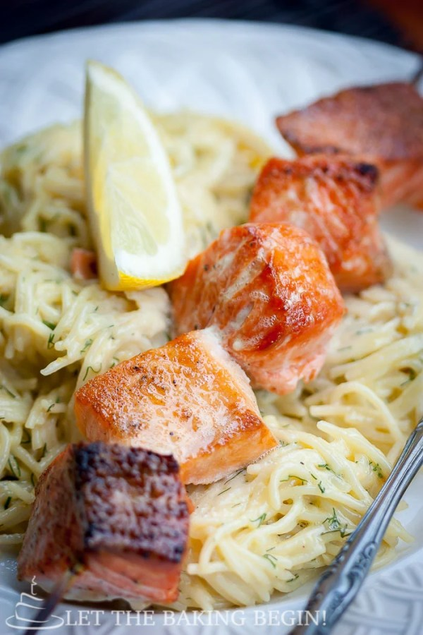 Side view of oven grilled salmon kabobs on top of spaghetti noodles and a fresh lemon in a white decorative bowl.