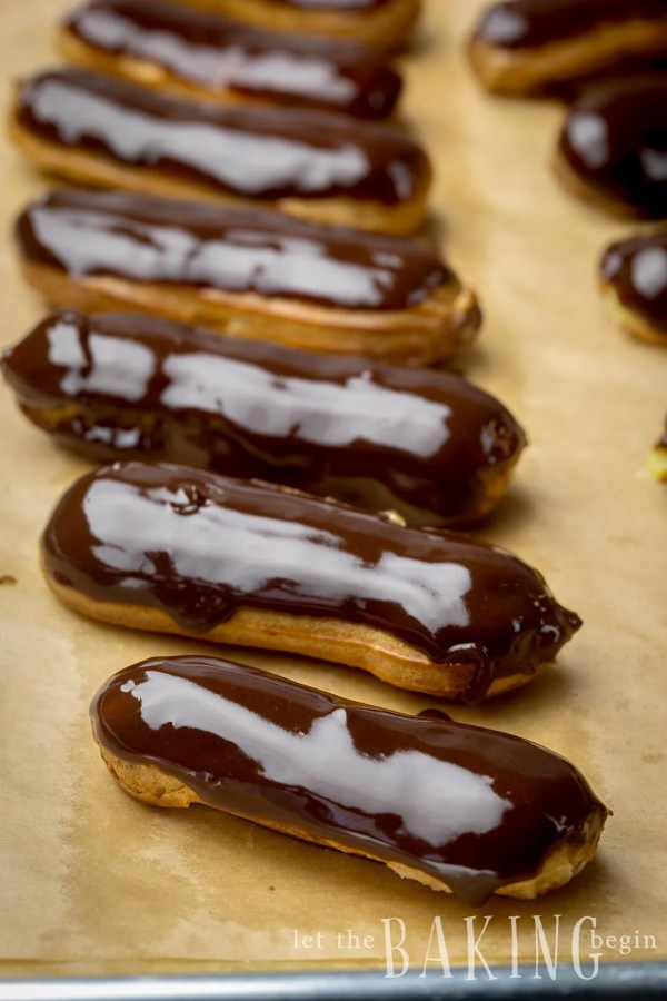 Classic eclairs dipped in chocolate lined in a row on parchment paper.