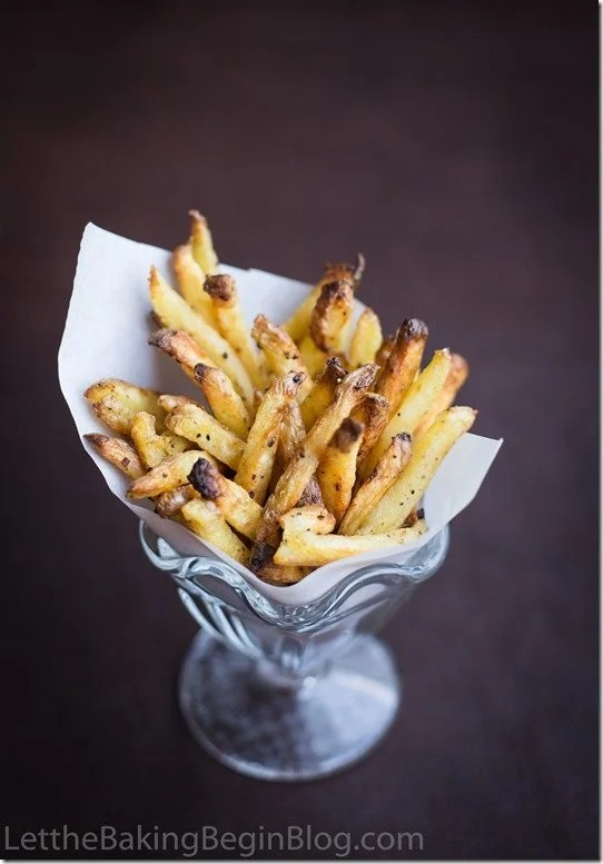 Oven baked fries in a glass cup topped with pepper.