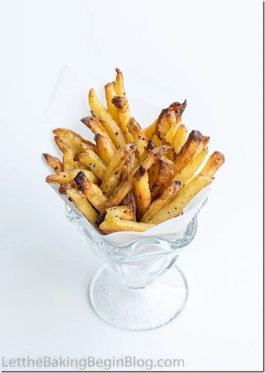 French fries topped with ground pepper in a cup with parchment paper.