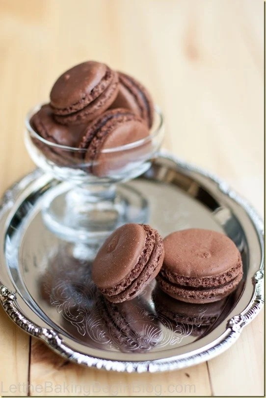 Two Dark Chocolate Truffle Macaron recipe on a tray with some in a cup.