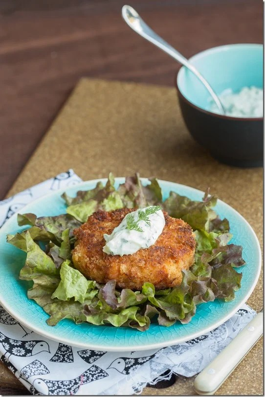 Salmon cake on top of plate of romaine topped with tzatziki sauce and fresh greens on a decorative plate.
