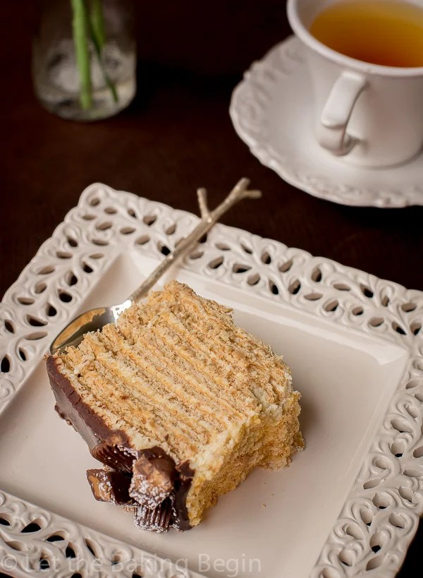 Soft and sweet no bake honey cake on a plate with a spoon next to a cup of tea.