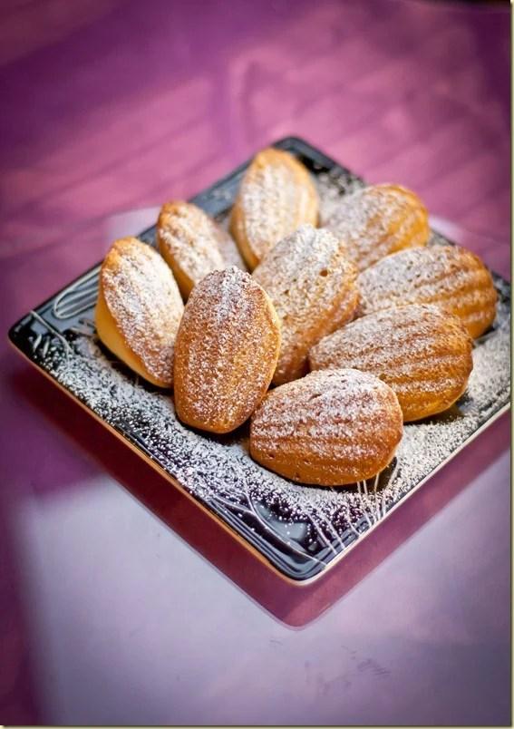 Lemon madeleines on a black decorative plate sprinkled with powdered sugar.