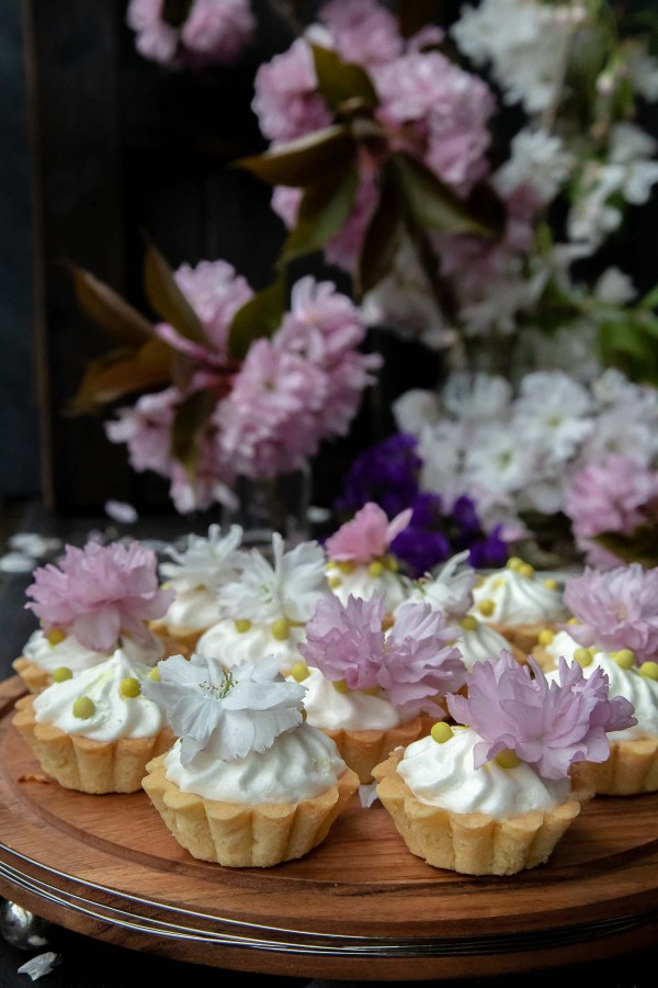 Mini tart recipe - small tarts topped with souflee and fresh flowers on a cake stand.