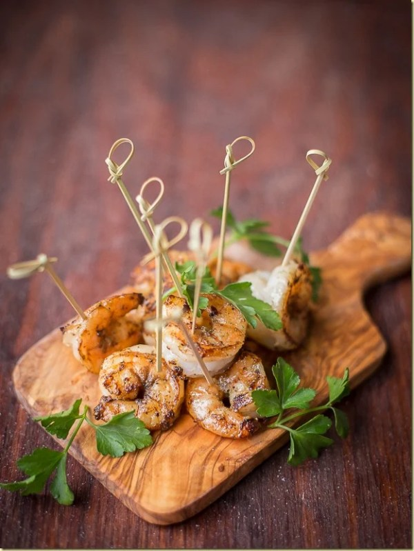 Sauteed garlic shrimp with toothpicks on a cutting board.