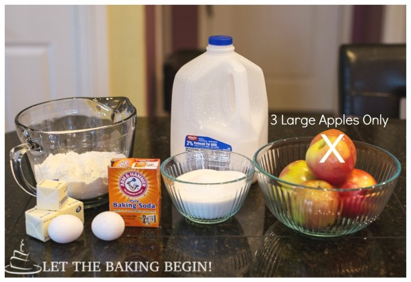 Flour, butter, eggs, baking soda, sugar, milk, and apples displayed on a black counter top.
