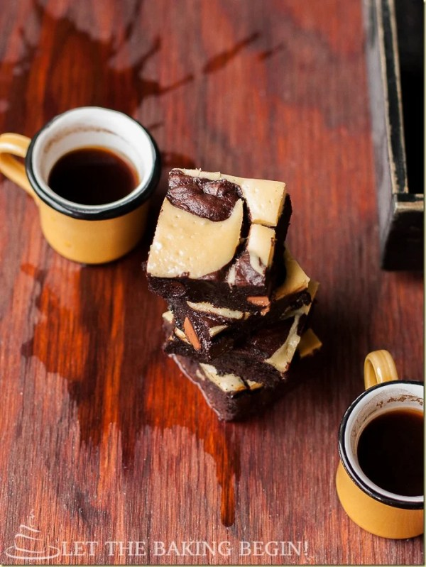 Cream cheese brownies stacked on a table with spilled coffee and two coffee mugs.