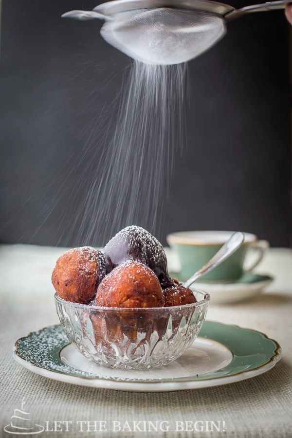 Donuts topped with chocolate ganache and powdered sugar in a glass bowl on a green and white decorative plate.