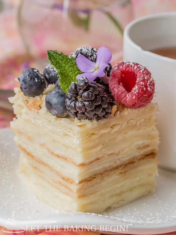 Piece of cake topped with blueberries, raspberries, blackberries, mint, and powdered sugar on a white decorative plate with a cup.