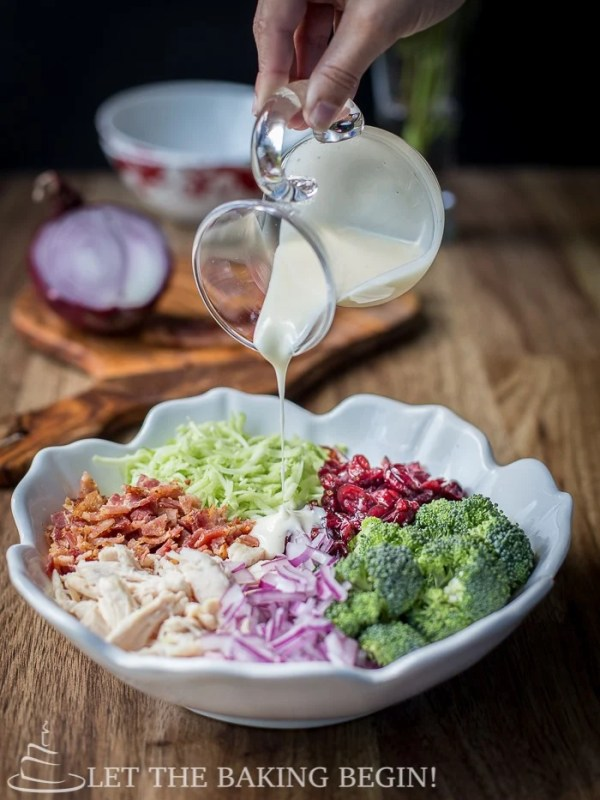 Dressing being poured on broccoli salad in a white decorative bowl on a wooden table.