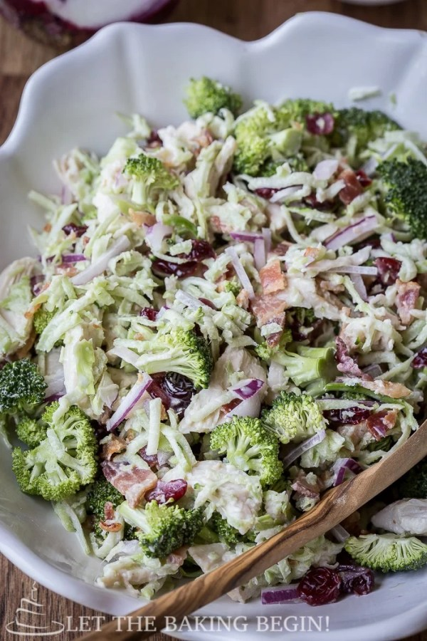 Mixed broccoli salad in a white bowl with a wooden spoon.