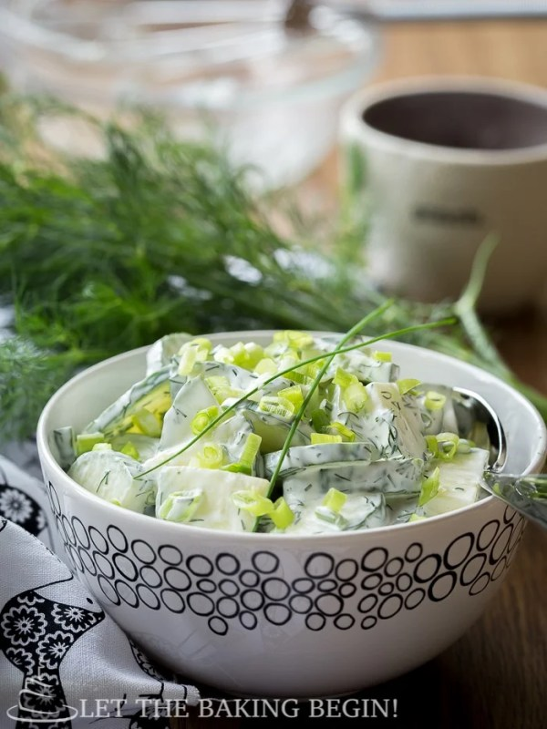 Side view of cucumber dill salad topped with fresh greens in a white decorative bowl on a wooden table.