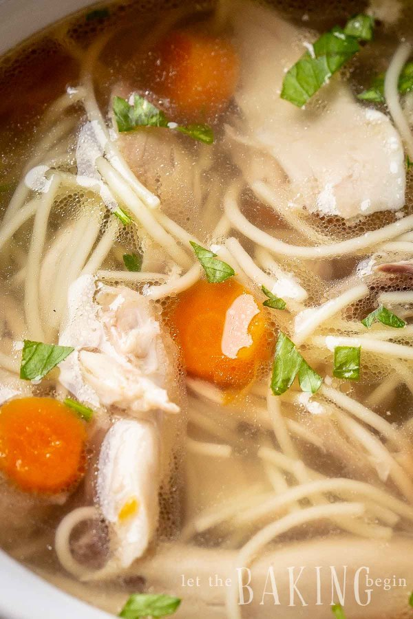 Close up picture of chicken noodle soup topped with greens.