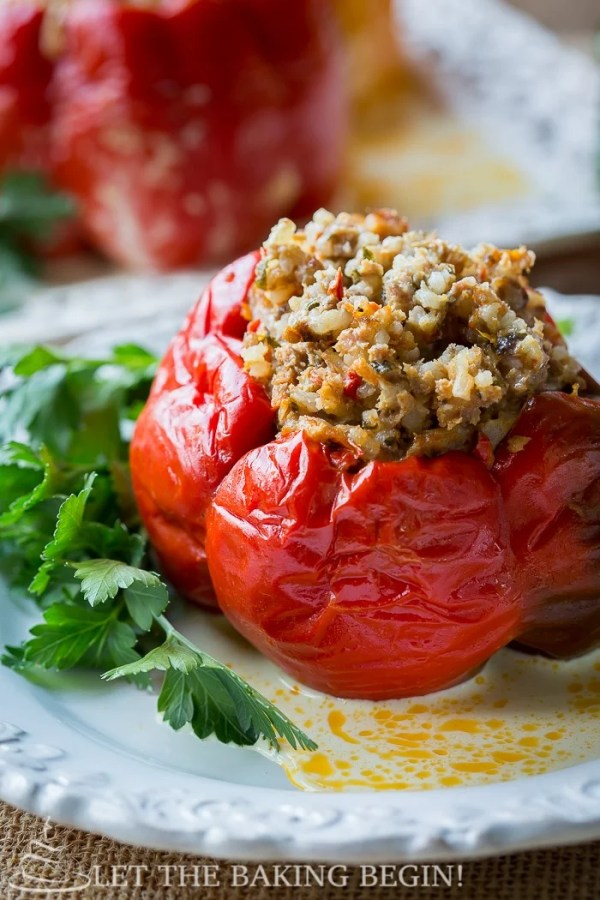 Stuffed red pepper on a white decorative plate with fresh greens.