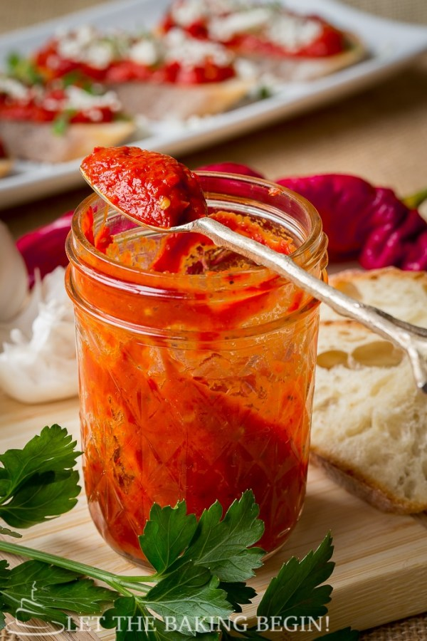 Spicy roasted pepper dip in a mason jar with a metal spoon.