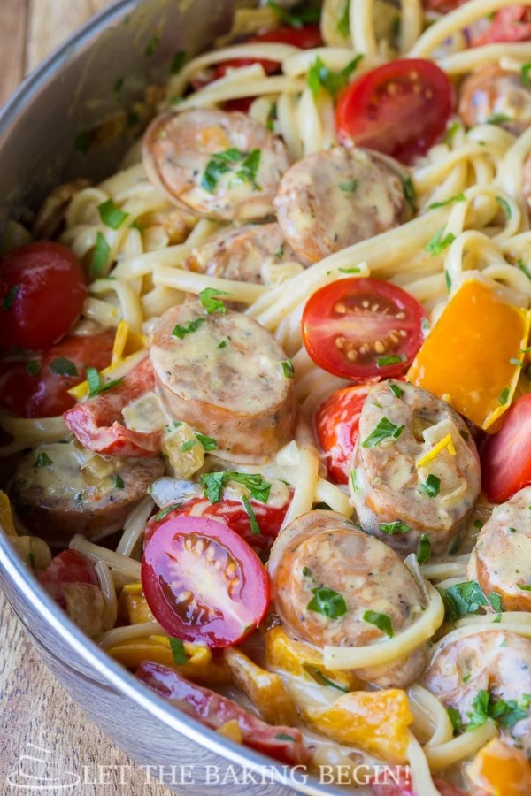 Sausage pepper fettuccine in a skillet with parsley and tomatoes.