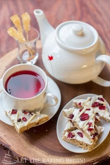 Cranberry bliss bar on a white plate with a cup of tea in a white mug next to a tea kettle, and another plate of cranberry bliss bars.
