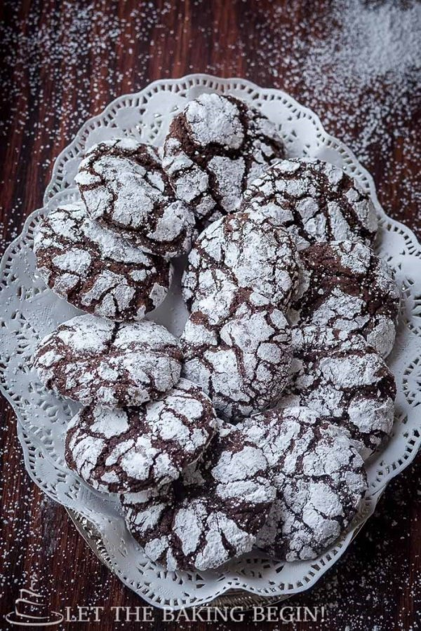 Top view of chocolate crinkle cookies on a decorative plate topped with powdered sugar.
