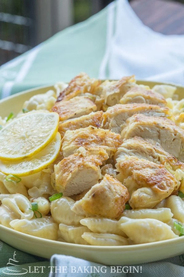 Side view of garlic shells topped with fried chicken and fresh lemon slices in a yellow decorative plate.