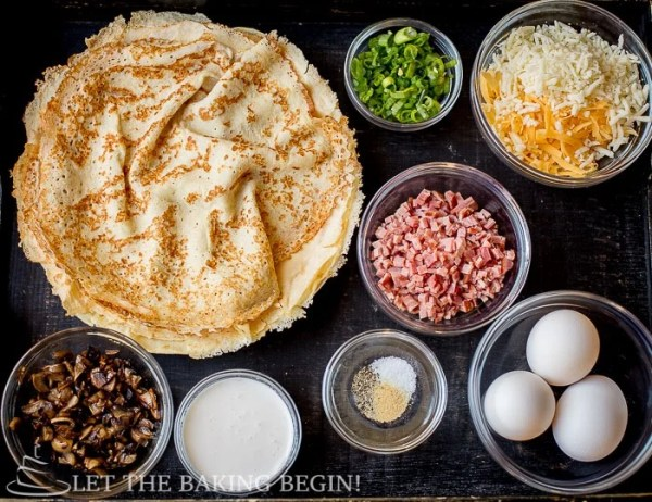 Cooked crepes, chopped mushrooms, diced ham/polish sausage, cheese, chopped chives or scallions, eggs, cream or milk, salt, pepper, garlic powder, and chopped parsley on a black wooden tray.