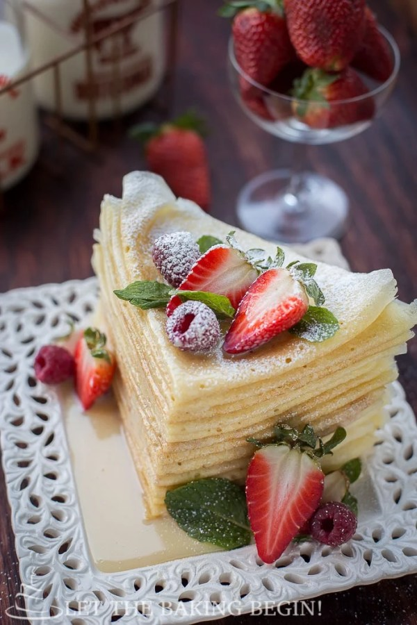 Folded crepes on a white plate topped with berries and sprinkled with powdered sugar.