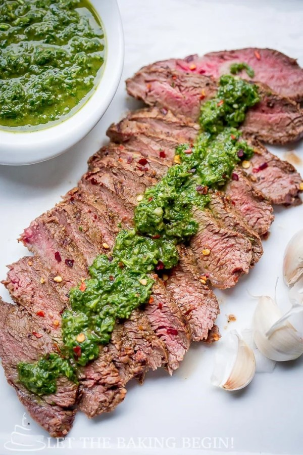 Steak topped with chimichurri sauce on a white plate sided with garlic and a bowl of chimichurri sauce.
