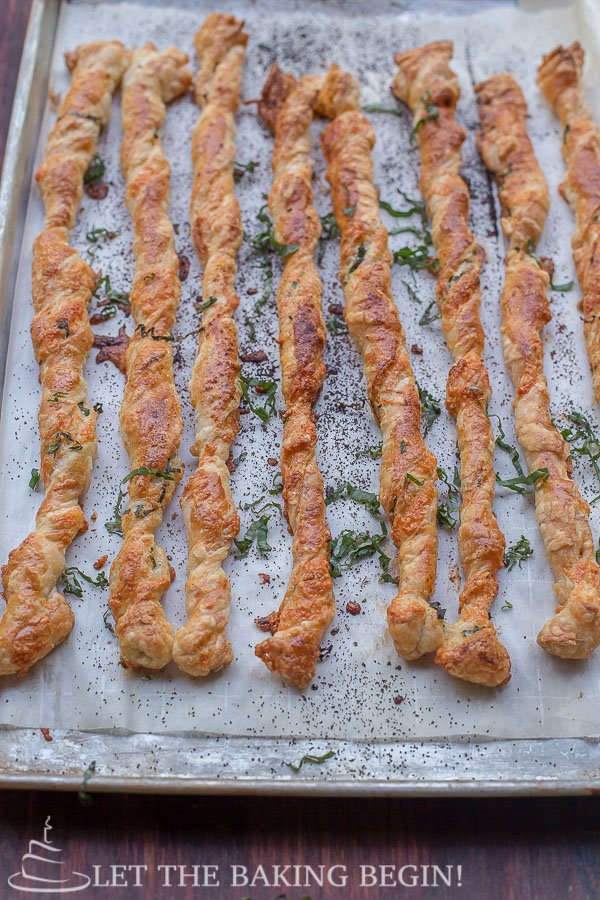 Cheese and Basil Puff Pastry Twists on a baking sheet topped with cheese and basil.