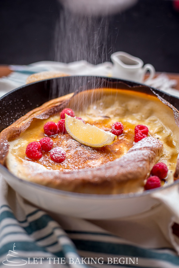 German pancake topped with raspberries, lemon, syrup and powdered sugar in a pan.