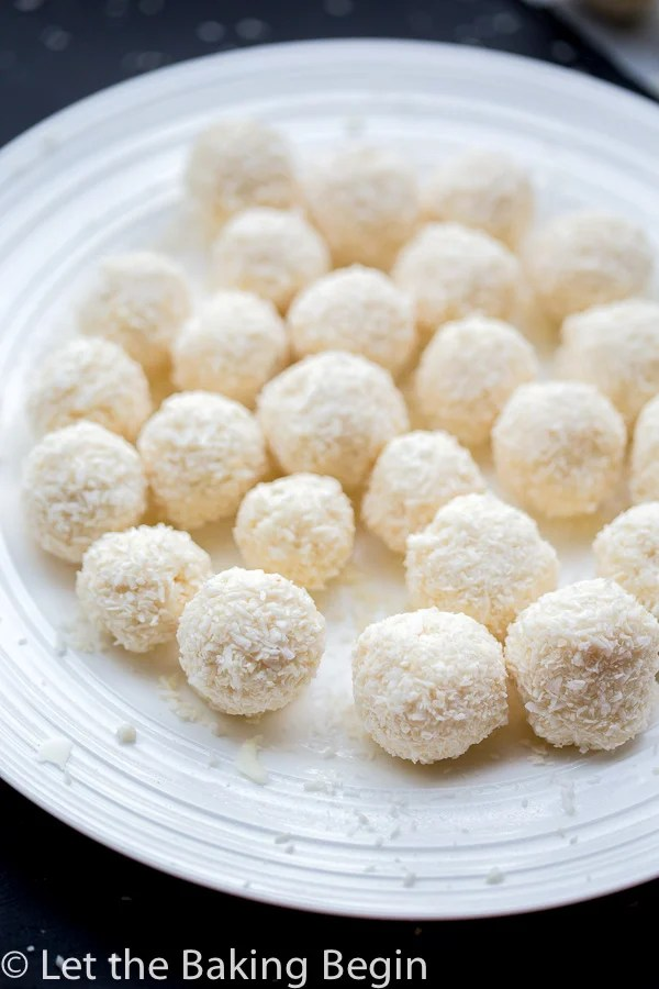 White chocolate coconut candies on a plate covered in coconut shavings.