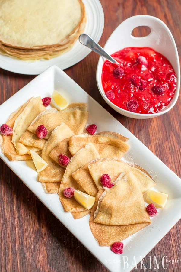Crepes topped with fresh raspberries and lemons on a white decorative plate with strawberry and raspberry jam in a white decorative bowl.