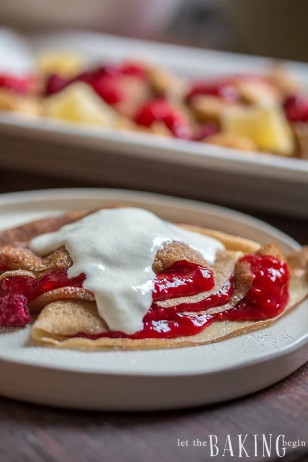 Crepes topped raspberry and strawberry jam and sweetened sour cream.