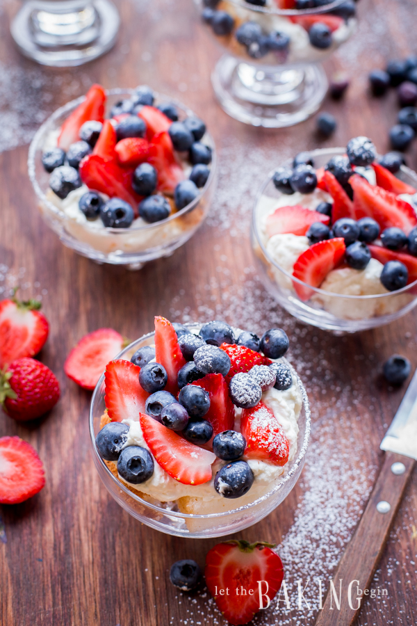Cheesecake and berry trifles with blueberries and strawberries in glass cups topped with powdered sugar on a wooden board with cut strawberries and a knife
