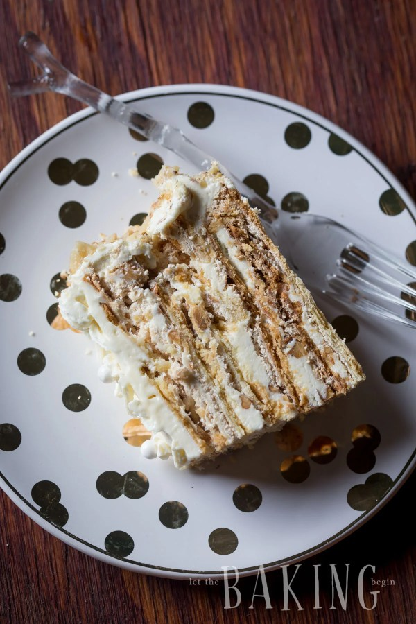 A slice of shortbread cake with layers of meringue and walnuts on a plate with a fork.